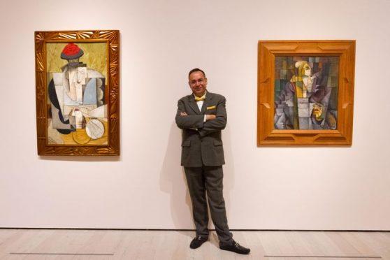 """SHM62 - LOS ÁNGELES (CA, EEUU), 07/12/2016.- El curador del Museo del Palacio de Bellas Artes, Juan Rafael Coronel Rivera, posa junto a una obra de su abuelo el artista mexicano Diego Rivera en la exhibición """"Picasso y Rivera: conversaciones a través del tiempo"""" hoy, miércoles 7 de diciembre 2016, en la sede del Museo de Arte Contemporáneo de Los Ángeles (LACMA), en California (EE.UU.). Con más de 100 pinturas y grabados firmados por los pintores Pablo Picasso y Diego Rivera, figuras estandartes de las artes plásticas del pasado siglo, la exhibición muestra el diálogo que surge entre las obra de los dos pintores, su formación en el cubismo y la relación que establecieron con la época que vivieron. EFE/Felipe Chacón"""
