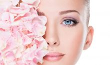 Closeup portrait of young beautiful woman  with  the flowers near the eyes. Face of a model with pink makeup  - isolated on white background