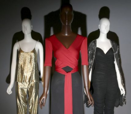"A dress by Scott Barrie, center, is displayed with other clothes at the opening of the ""Black Fashion Designers"" exhibit at the Fashion Institute of Technology in New York, Tuesday, Dec. 6, 2016. Running through May 16, the show offers a glimpse into exactly how impactful designers of color have been through the decades. (AP Photo/Seth Wenig)"